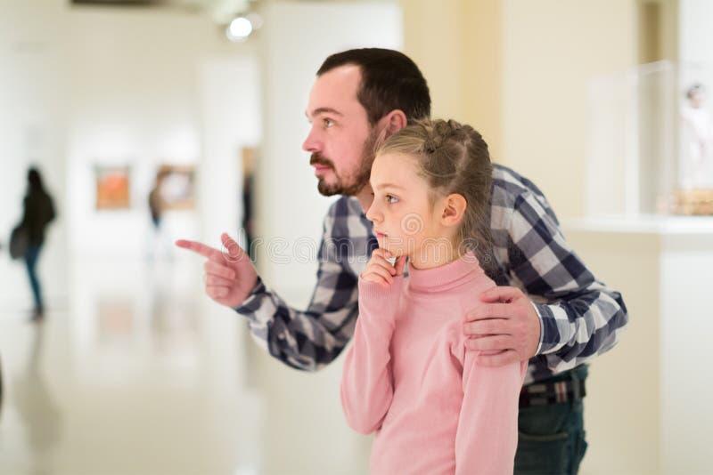 殷勤父亲和女儿探索的博览会在博物馆 免版税库存图片