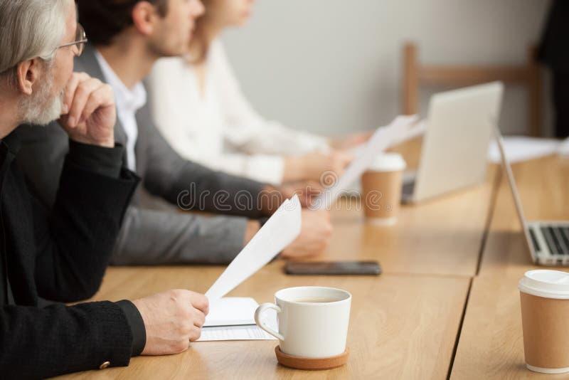 殷勤资深商人集中于听在小组meeti 免版税图库摄影