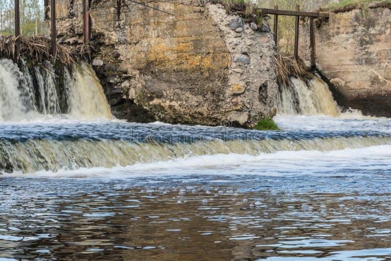 毁坏老被毁坏的水坝、支持获得石头和混凝土,水的潮流形成小瀑布 库存照片