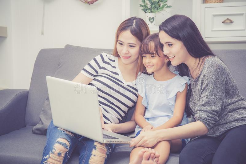 母亲、有的伯母和的孩子一起lerning与使用的时间便携式计算机与在家放松和愉快在长沙发 库存照片