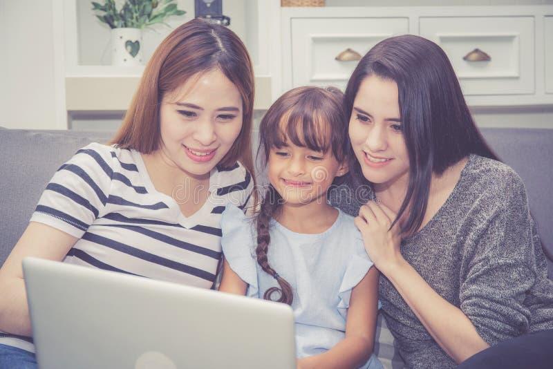 母亲、有的伯母和的孩子一起lerning与使用的时间便携式计算机与在家放松和愉快 免版税库存图片