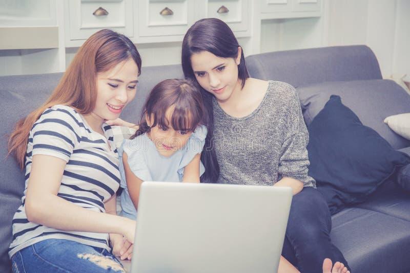 母亲、有的伯母和的孩子一起lerning与使用的时间便携式计算机与在家放松和愉快 库存图片