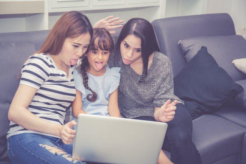 母亲、有的伯母和的孩子一起lerning与使用的时间便携式计算机与在家放松和愉快 免版税库存照片