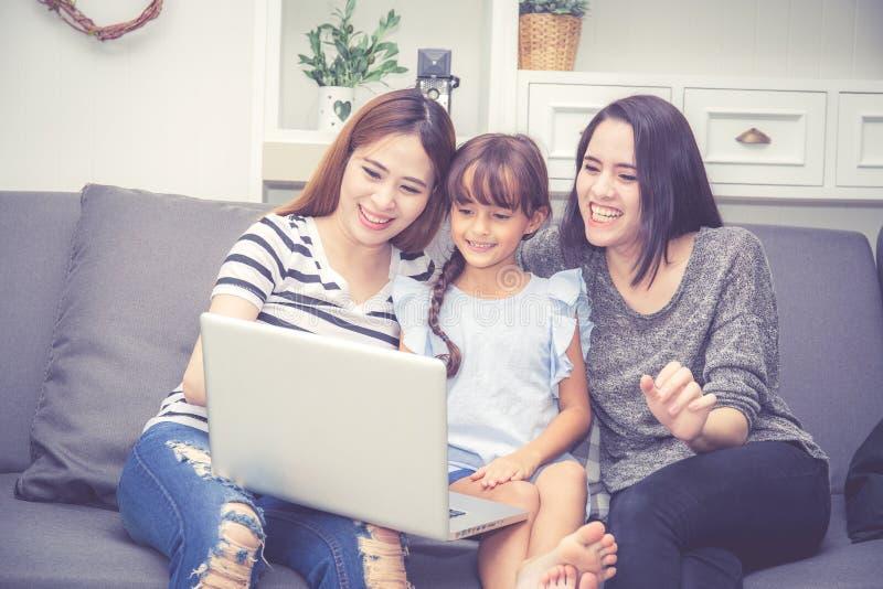 母亲、有的伯母和的孩子一起lerning与使用的时间便携式计算机与在家放松和愉快 库存照片