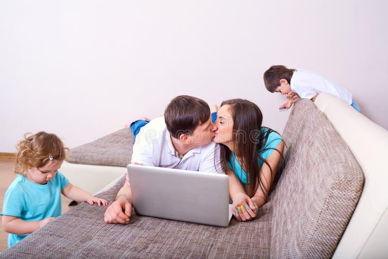 母亲、父亲、女儿和男孩,亲吻的父母,孩子家庭  免版税库存图片