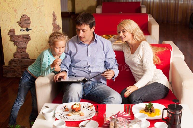 母亲、父亲和孩子咖啡馆的 库存照片