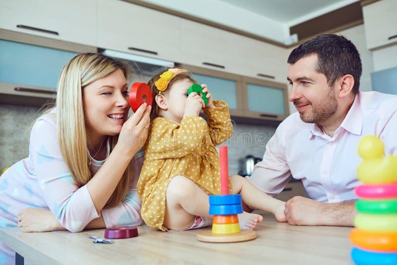 母亲、父亲和孩子在屋子里使用 免版税图库摄影