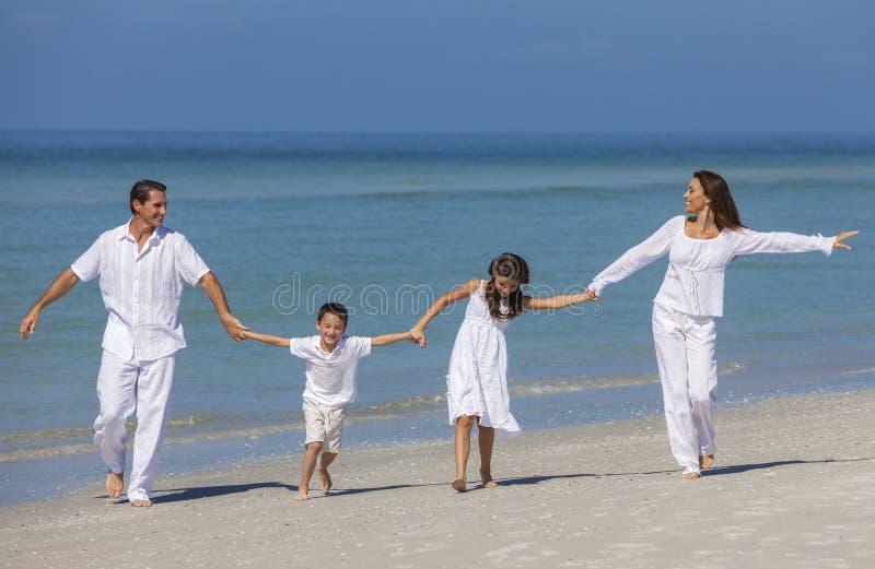 母亲、父亲和跑获得乐趣在海滩的儿童家庭 免版税库存图片