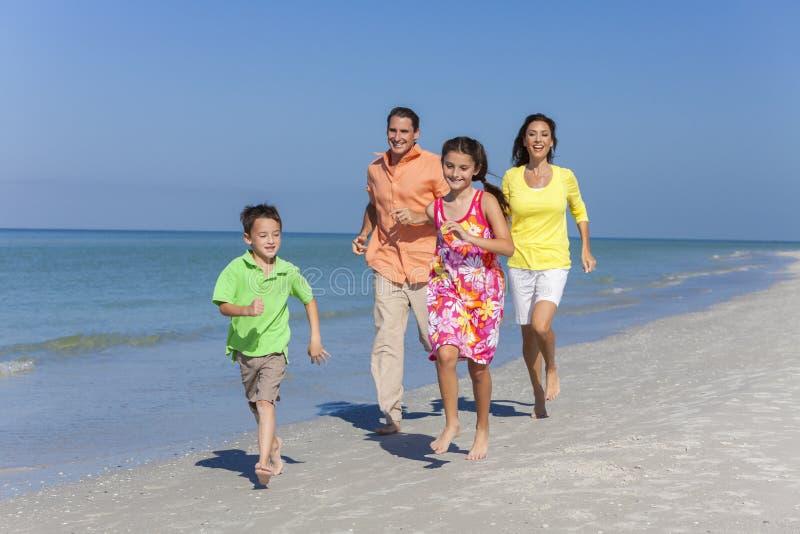 母亲、父亲和跑获得乐趣在海滩的儿童家庭 免版税库存照片