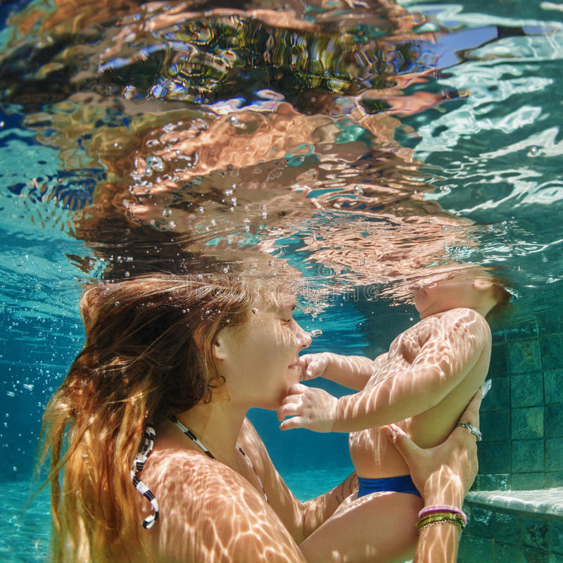 母亲、婴孩游泳和下潜水下在游泳池 图库摄影
