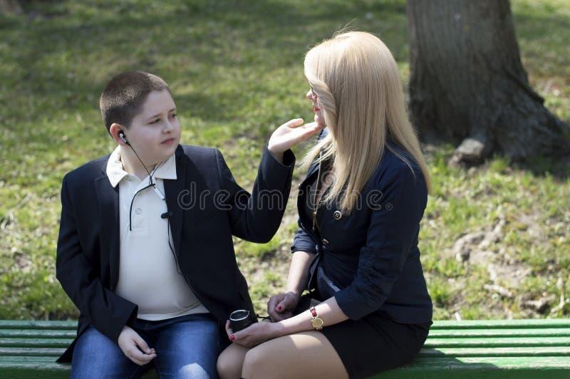 年轻母亲与孩子谈话,坐长凳 免版税库存图片
