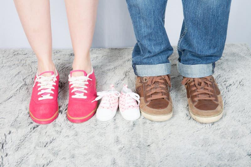 母亲与鞋子的父亲和婴孩脚家庭观念脚新出生的女孩的 库存图片