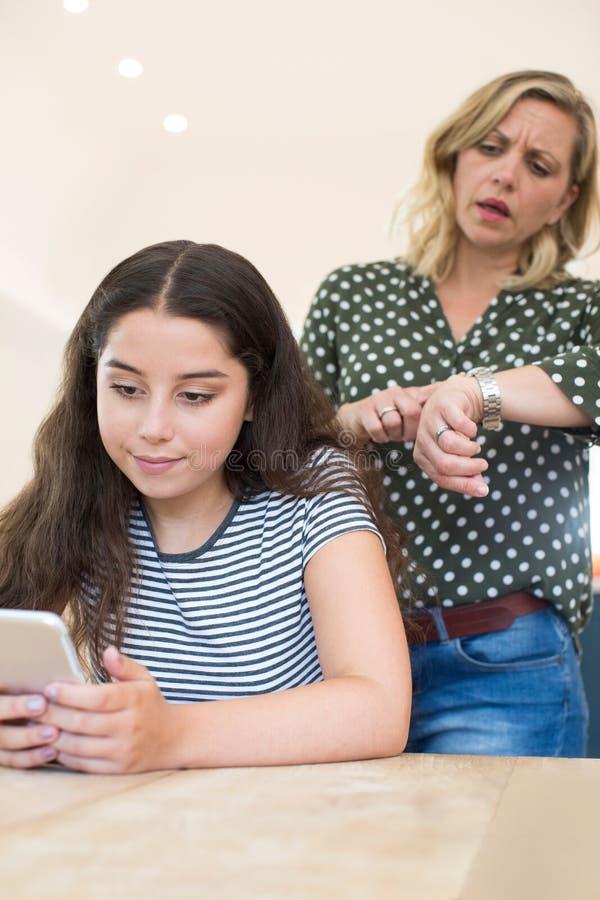 母亲争论与十几岁的女儿关于对手机的用途 库存照片