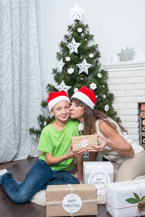 母亲亲吻她的儿子并且给礼物 免版税库存照片