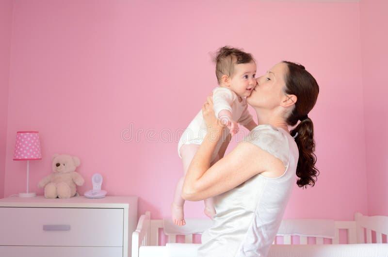 年轻母亲亲吻她的婴孩 免版税库存图片