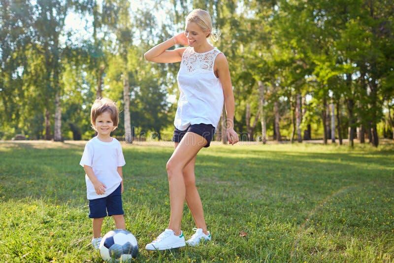 母亲使用与她的球的儿子在公园 图库摄影