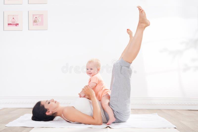 母亲做与她的婴孩的体操 免版税图库摄影