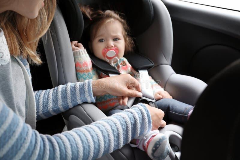 母亲儿童安全位子汽车的紧固婴孩 免版税图库摄影