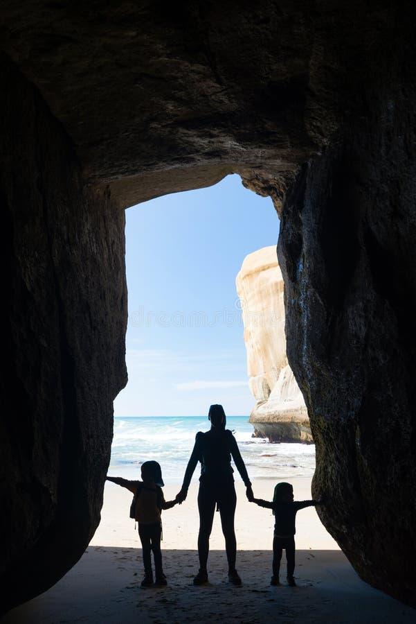 母亲剪影有两个孩子的在隧道海滩的一个洞 库存照片