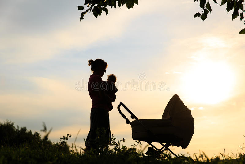 母亲剪影有小婴孩和婴儿推车的天空的 库存图片