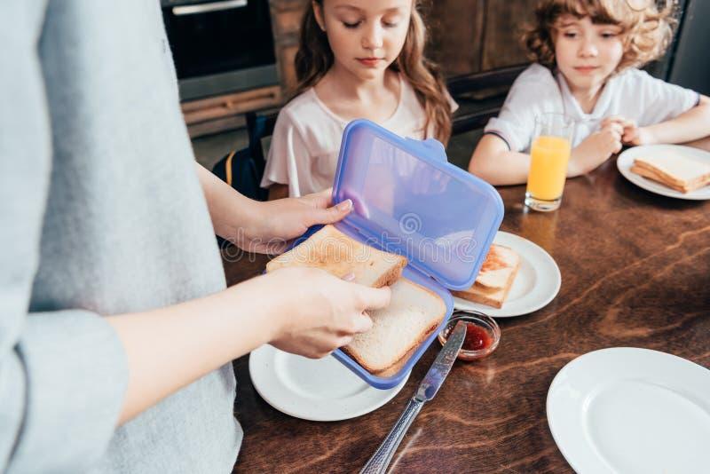 母亲包装在箱子的学校午餐 免版税库存图片