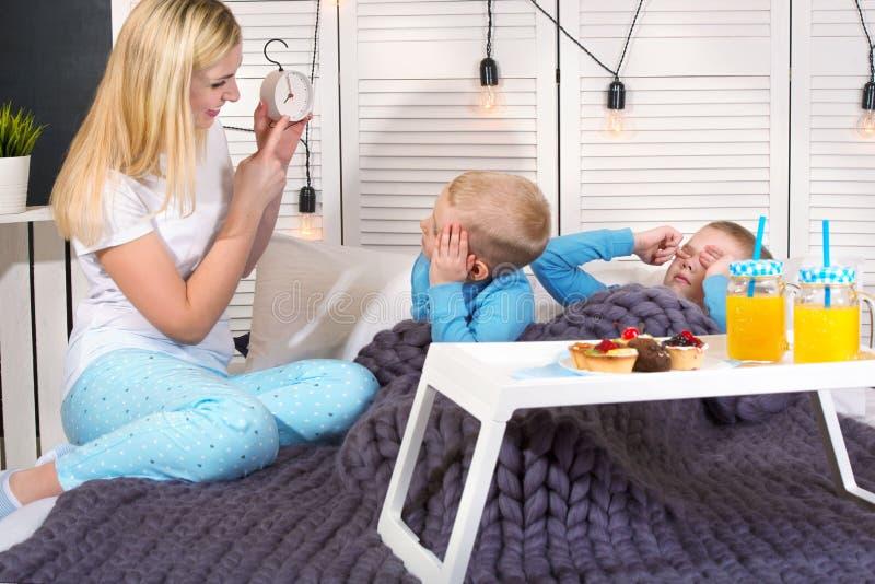 母亲叫醒她心爱的儿子 早餐在孩子的床,惊奇上 免版税库存照片