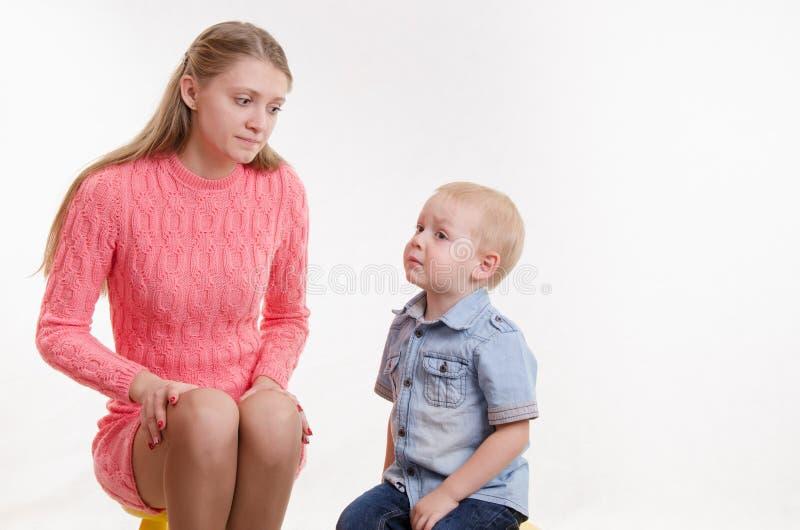 年轻母亲可耻地看他的年轻儿子 免版税库存照片