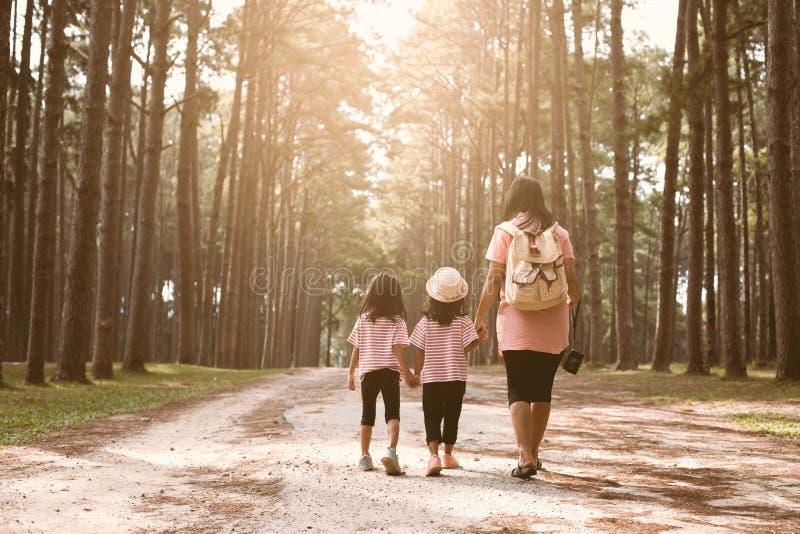 母亲和一起走儿童的女儿握手和 免版税库存照片