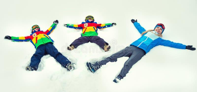 母亲和两个儿子在一个多雪的森林里走 家庭冬天乐趣为圣诞节假期 图库摄影