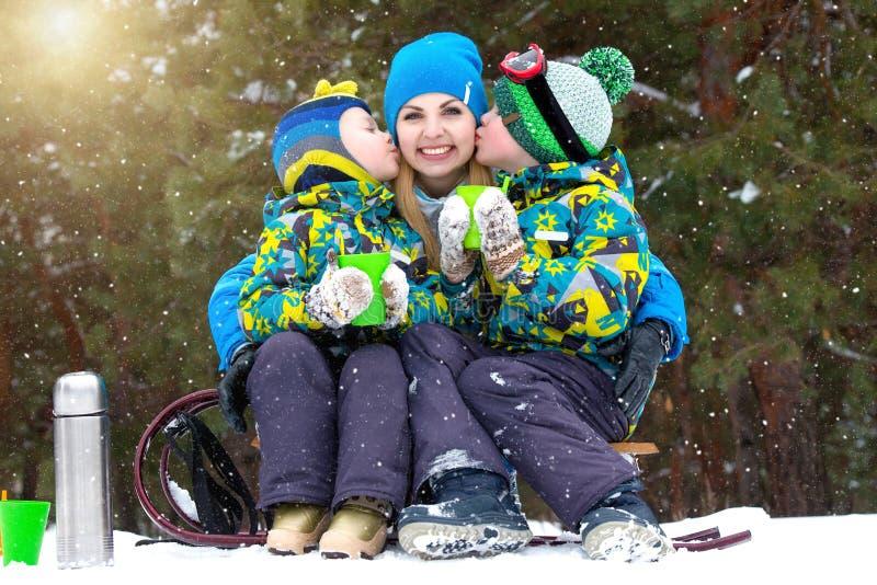 母亲和两个儿子在sledging以后喝热的茶在一个多雪的森林里 家庭冬天乐趣为圣诞节假期 库存图片