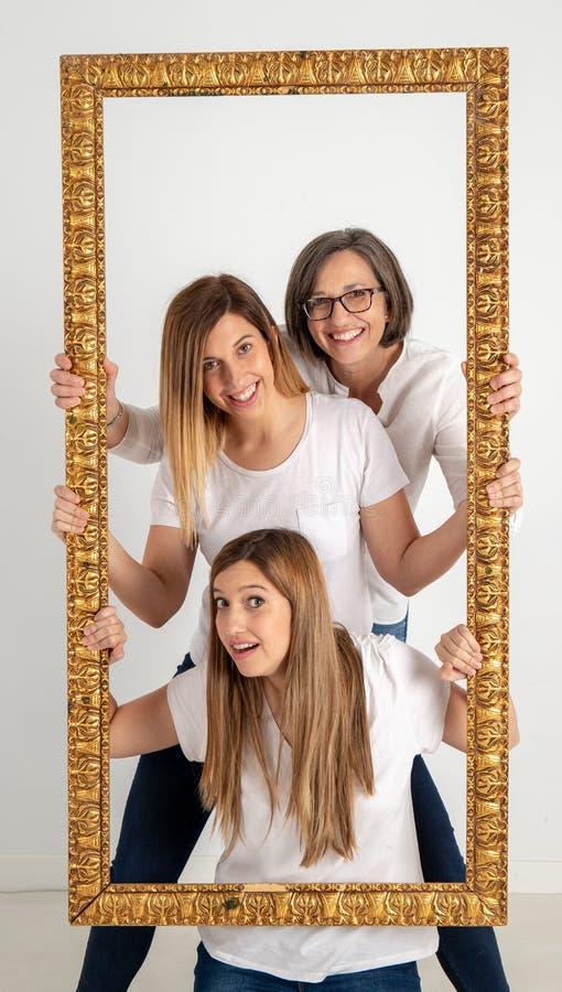 母亲和两个双姐妹在非常滑稽的态度享用 免版税库存图片