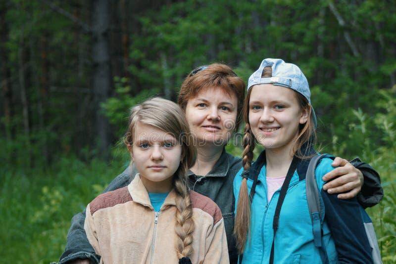 母亲和两个女儿少年在公园 库存照片