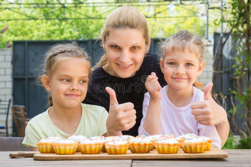 母亲和两个女儿显示翘拇指,并且穿戴复活节杯形蛋糕 免版税图库摄影
