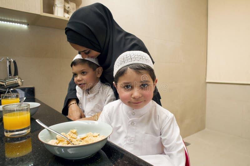 母亲和两个孩子阿拉伯家庭吃早餐早晨 免版税库存图片