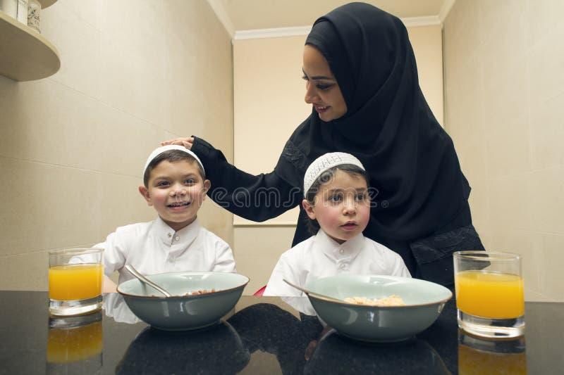 母亲和两个孩子阿拉伯家庭吃早餐早晨 库存照片
