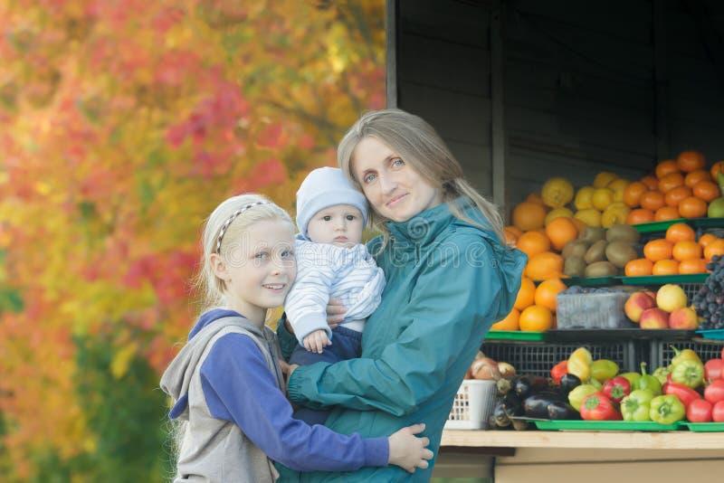 母亲和两兄弟姐妹秋天街道室外家庭画象明亮的秋天树离开和水果摊背景的 免版税图库摄影