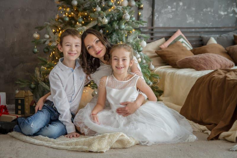 母亲和两childre在圣诞树下 免版税库存照片