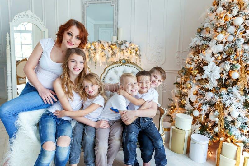母亲和五个孩子在圣诞树附近在家 免版税库存照片