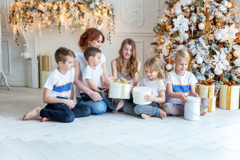 母亲和五个孩子在圣诞树附近在家 免版税库存图片