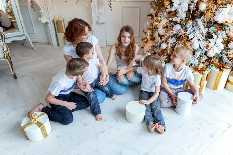 母亲和五个孩子在圣诞树附近在家 图库摄影