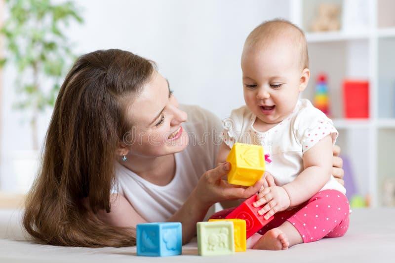 母亲和使用与发展玩具的女婴在客厅 免版税库存图片