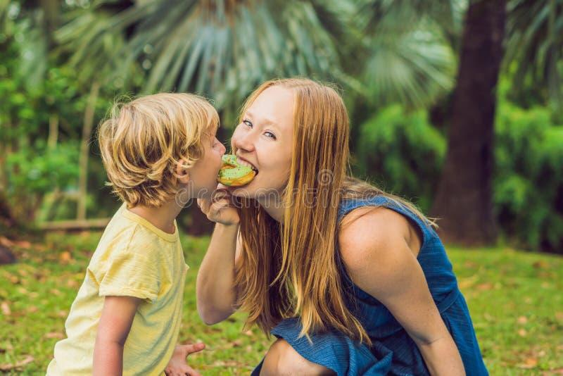 母亲和儿子在公园吃着一个多福饼 在家庭的有害的营养 免版税图库摄影