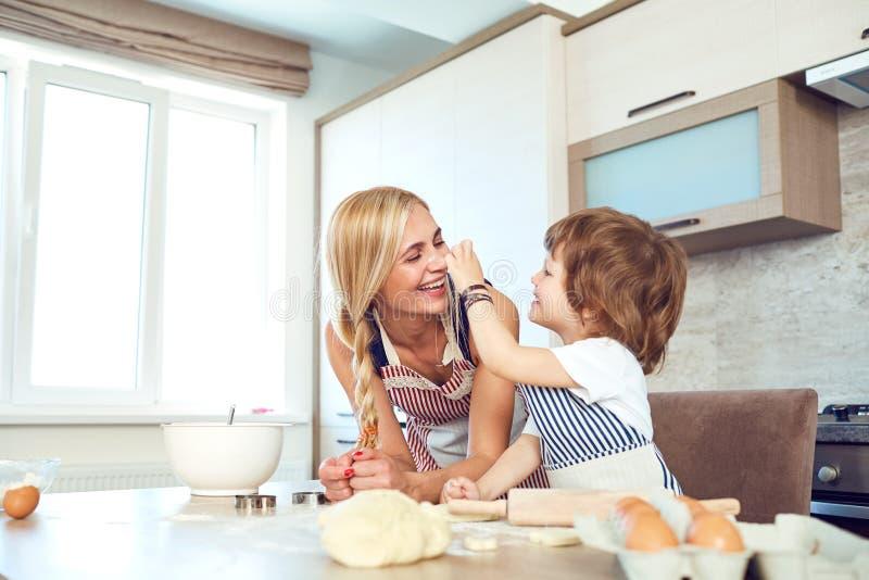 母亲和儿子在厨房里烘烤蛋糕 库存图片