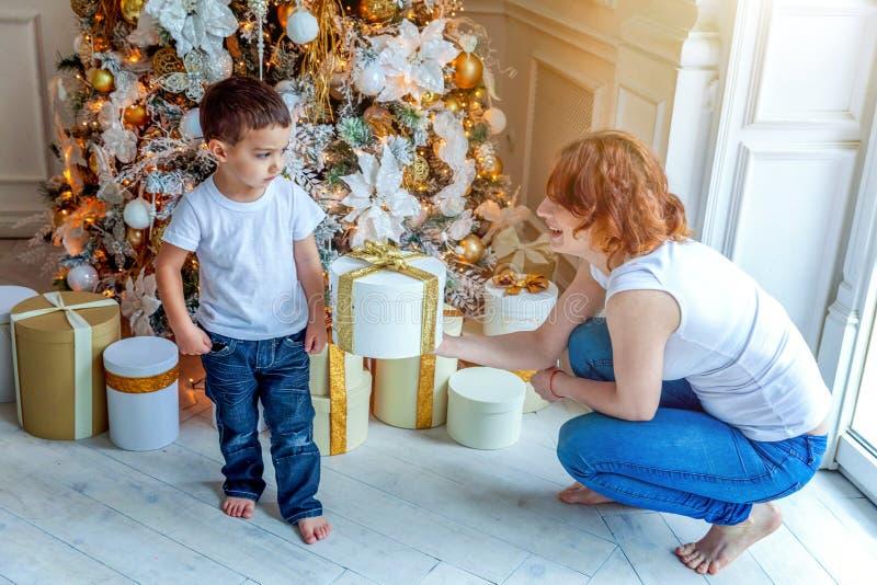母亲和儿子在圣诞树附近在家 库存图片