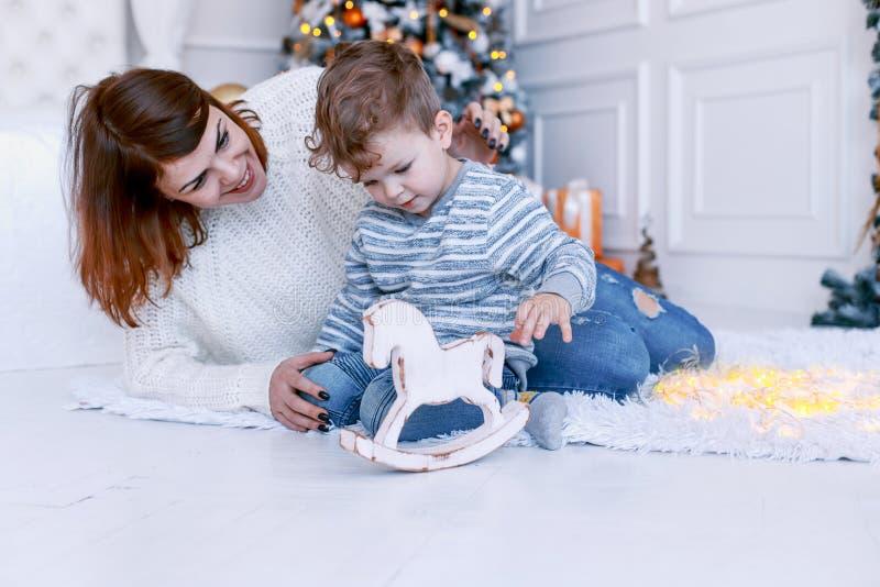母亲和儿子在圣诞树除夕前面 爱、幸福和大家庭概念 图库摄影