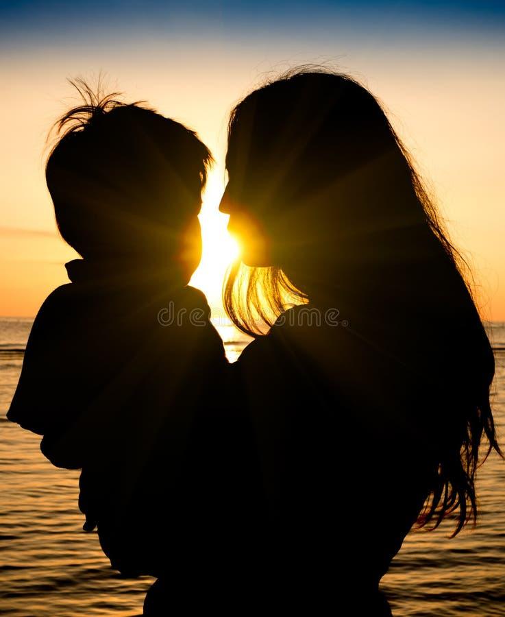 母亲和儿子在爱内的深刻的片刻在日落期间在海滩 免版税图库摄影