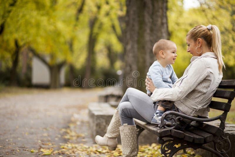 母亲和儿子在秋天森林里 库存照片
