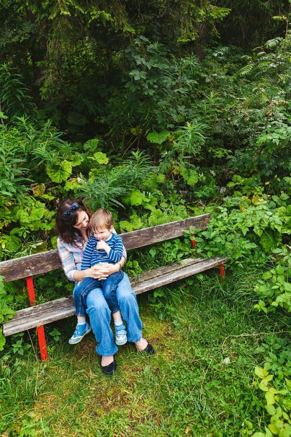 母亲和儿子坐公园长椅 库存图片