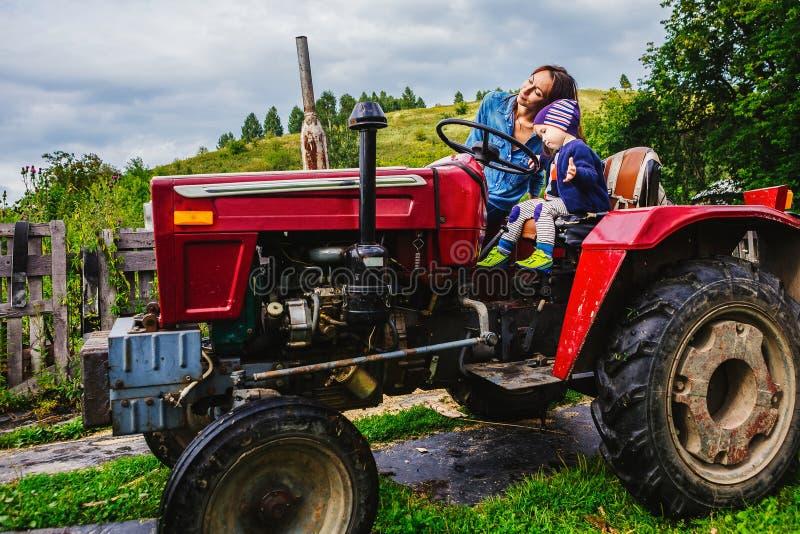 母亲和儿子坐拖拉机 免版税库存照片