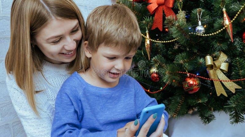 母亲和儿子有手机的在圣诞树附近一起坐 图库摄影